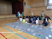 小清水図書館の司書さんの読み聞かせを聞く児童達の写真