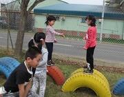 タイヤの遊具で遊ぶ児童達の写真