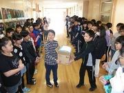 雑巾を渡す卒業生代表と受け取る児童会長、その様子を見守る在校生と卒業生の写真